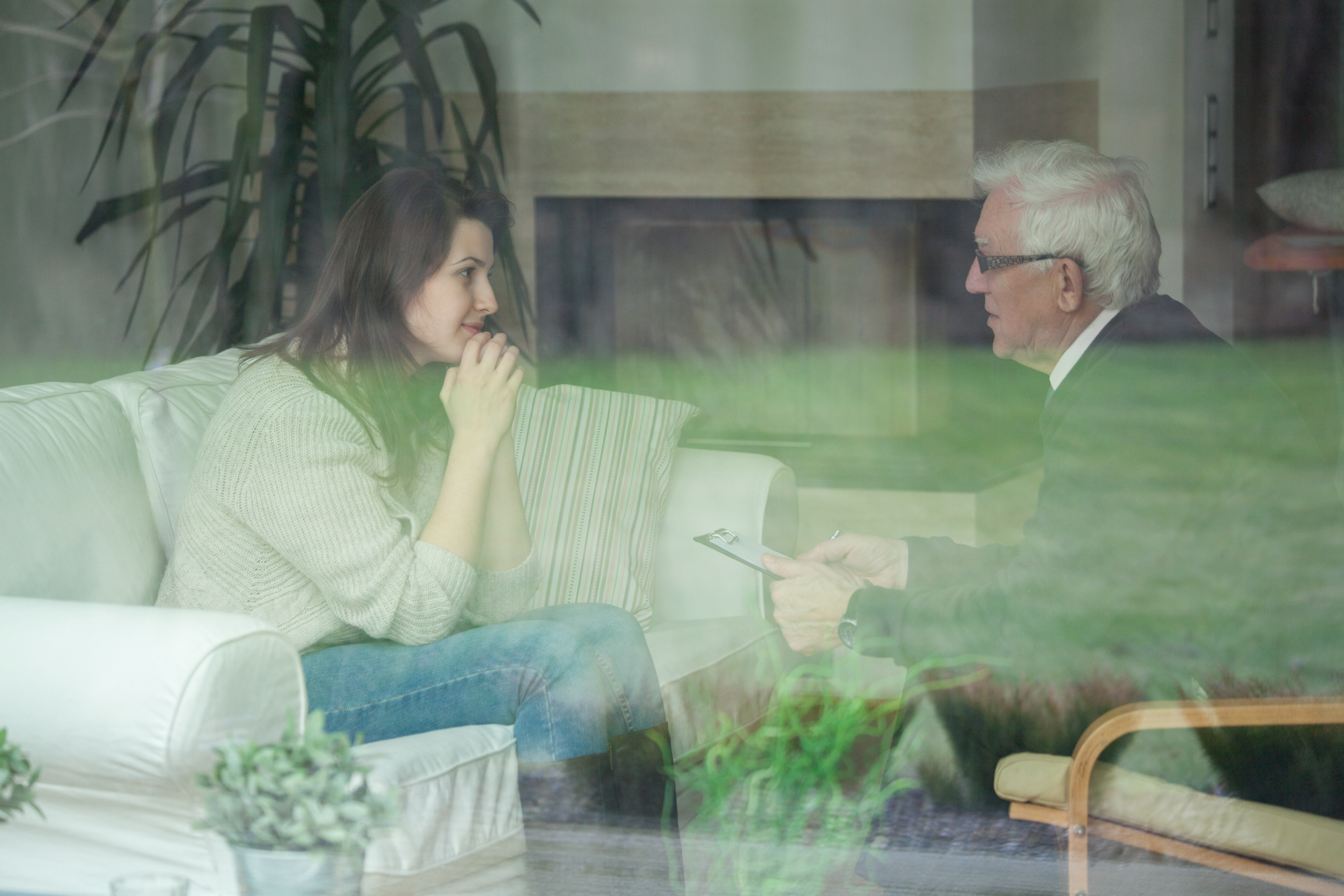 Elder therapist consulting young patient at home